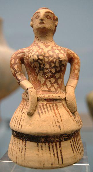 Mujer vestida a lo cretense: vestido con mangas y falda con volantes, trenza, pendientes, pulseras y collar. Terracota de Esparta, h. 1400 a. C.